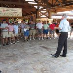 A man addresses a huge group of golfers outside the building