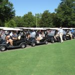 A lineup of the golf carts with all the golfers in them