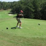 A golfer in a black shirt and red cap takes a swing