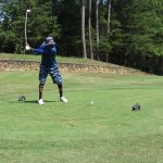 A golfer in a blue shirt and blue shorts at the apex of a golf swing