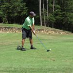 A golfer in green shirt and dark grey shorts gets ready to swing