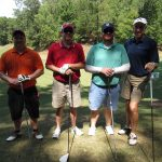 A team of four golfers, one in an orange shirt, one in red, one in aqua, and one in a dark ble