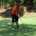 A golfer in an orange shirt and red hat about to swing