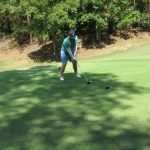 A golfer in a green shirt and jeans shorts starts a swing