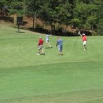 A distant shot of a team of 4 golfers gather around a hole