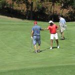 A closer shot of 3 golfers gather around a hole