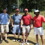 A team of four golfers, two in blue shirts and two in red