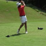 A golfer in a red shirt and white shorts ends his swing