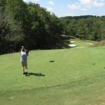 A long shot of the drive with a golfer in grey at the front