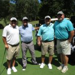 A team of four golfers, one in a white shirt, one in light blue, and two in aqua
