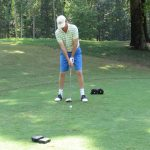 A golfer in a green and white shirt adjusting his swing