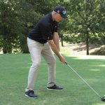 A golfer in black shirt and tan pants starts a swing