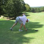 A golfer in a white shirt places his ball