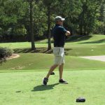 A golfer in a black shirt and tan shorts finishes his swing