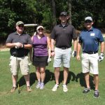 A team of four golfers, two in dark grey shirts, one in navy, and one in purple