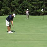 A golfer in a black shirt sets up a shot while his team mate in back watches