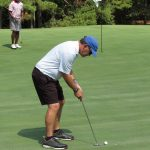 A golfer in a white shirt and black shorts sets up a shot while his teammate watches