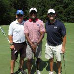 A team of three golfers, one in a black shirt, one in white, and one in red striped