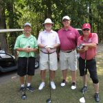 A team of four golfers, one in light green, two in red, and one in a pink tinged white