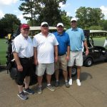 A team of four golfers, two in shades of blue, two in white