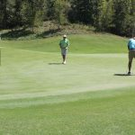 A golfer in a green shirt walks towards a teammate in a blue shirt