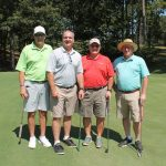 A team of four golfers, one in a light green shirt, one in grey, one in red, and one in aqua