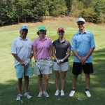 A team of four golfers, one in a pink shirt, one in blue, one in grey, and one in white