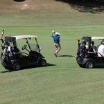 A golfer in a dark blue shirt hits a ball near two golf carts