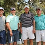 A team of four golfers, two in aqua shirts and one in grey with the other in black and white stripes