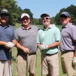 A team of four golfers, one in a light blue shirt and the others in light grey and dark grey