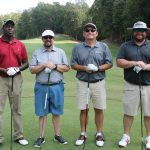 A team of four golfers, one in red shirt and the other in various shades of grey