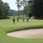A team of 4 golfers walking past a sand trap