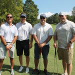 A team of four golfers, all in white shirts with the last one having grey stripes