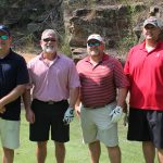 A team of four golfers, three in varying red shirts and one in black