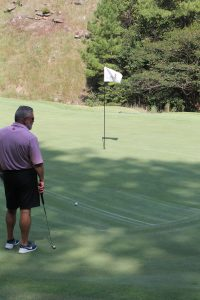 A golfer in dark shorts stands in the shade next to a flagged hole