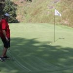 A golfer in a red shirt and dark shorts stands in the shade next to a flagged hole