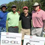A team of four golfers stand in front of two company signs