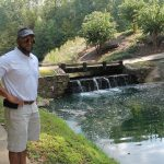 A golfer stands next to a small water fall
