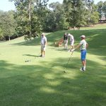 A group of four golfers talking on the green