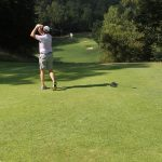 A golfer in tan pants and white hat hits a ball down the thoroughfare