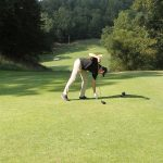 A golfer in black shirt and khaki pants places a ball
