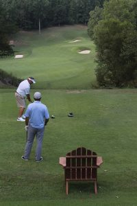 A chair on the field along with two golfers playing