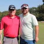 A team of two golfers, one in a red shirt one in white