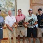 Dean of Engineering with a winning team holding elephant trophies that have their trunks down
